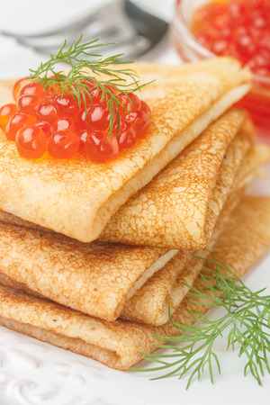 blini: Traditional Russian pancakes (blini ) with salmon caviar on a white plate. Selective focus