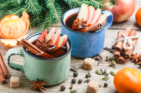 Mulled wine with Apple, citrus, cinnamon, cardamom and star anise on wooden background. Traditional hot Christmas and new years drink. Selective focus