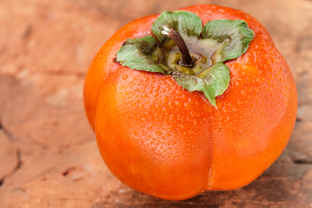 Fresh ripe persimmon with water drops. Selective focus. Copy space Stock Photo