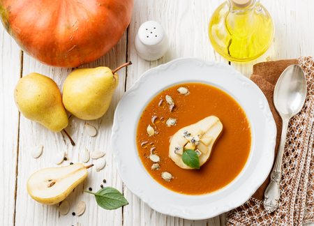 Delicious pumpkin soup with pear and blue cheese in a white plate. Vegetarian cuisine. Selective focus Stockfoto