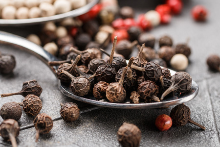 Black (cubeb), pink and white pepper in spoon on black table. Multicolored spice closeup. Selective focus