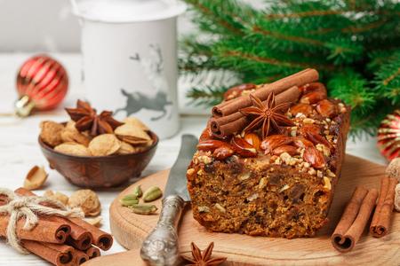 Eigengemaakte vakantie Vruchtencake met noten, vruchten en kruiden. Amandelen, kaneel, steranijs, kardemom op tafel. Traditioneel Engels gebak. Kerstmis. Nieuwjaar. Selectieve aandacht