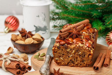 Homemade holiday Fruitcake with nuts, fruits and spices. Almonds, cinnamon, star anise, cardamom on the table. Traditional English pastries. Christmas. New year. Selective focus
