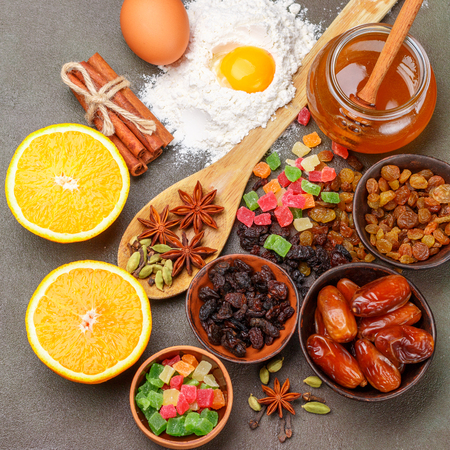Baking a fruitcake. The ingredients on the table - dark and light raisins, dates, flour, eggs, honey, cinnamon, star anise, cardamom, candied fruit, orange. Traditional holiday pastries. Christmas. New year. Selective focus Stock Photo