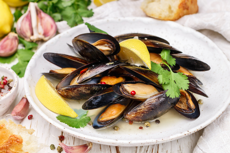 Delicious mussels in white wine with lemon, garlic, herbs and spices in a white plate. Baguette, Cilantro and pepper. Seafood. Clams in the shells. Snack for gourmets. Selective focus