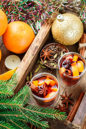 Mulled wine - Christmas hot drink with orange, cinnamon, cardamom and anise in a glass cups. New year. Selective focus