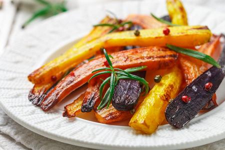 ローズマリー、粗海塩、コショウのローストニンジン。カラフルな野菜とスパイス。ベジタリアン料理。選択フォーカス