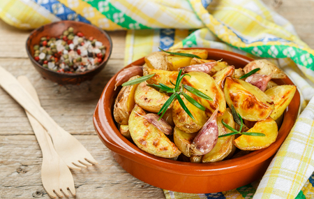 Potato wedges baked with garlic, rosemary and spices in a ceramic form. Selective focus