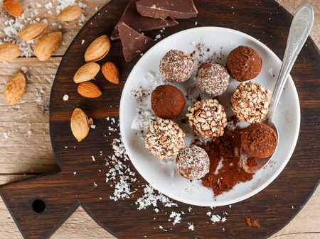 Prepare assorted dark chocolate truffles with cocoa powder, coconut and chopped almonds closeup. Homemade candy. Selective focus