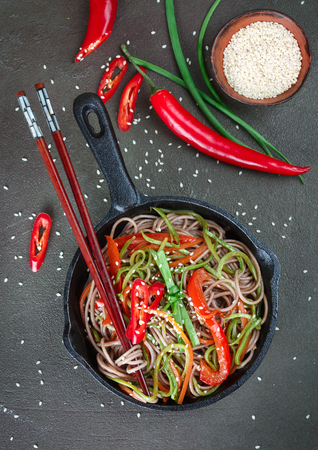 Buckwheat soba noodles with carrots, peppers, zucchini, green onion and sesame seeds - a traditional dish of Asian cuisine. Vegetarian dish. Selective focus Stock Photo