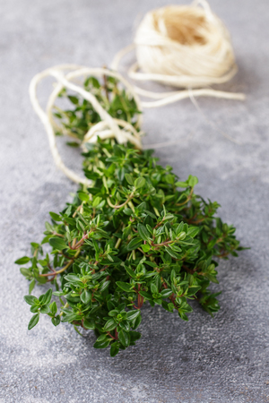 Sprigs of fresh organic thyme on a stone or concrete table. Herbs. Selective focus Фото со стока