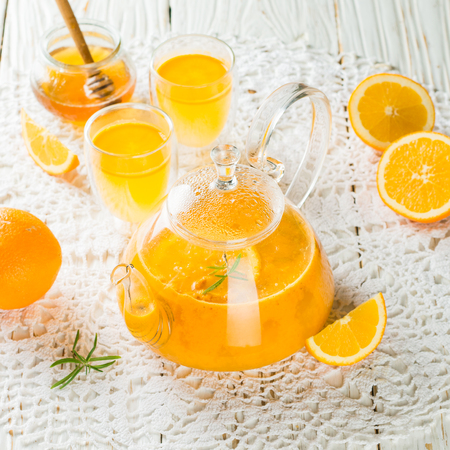 Tea made from sea buckthorn or cloudberries with orange and rosemary. Hot vitamin drink. Selective focus Stock Photo