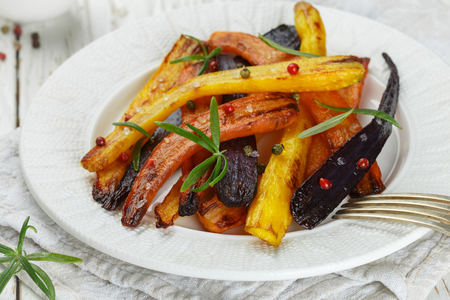 Baked carrots with rosemary, coarse sea salt and pepper. Colorful vegetables and spices. Vegetarian dish. Selective focus Stock Photo