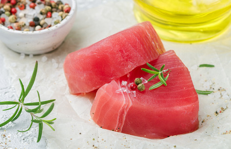 Raw Tuna fish steaks with sea salt, pepper and rosemary for grill or cooking. Prepare a delicious dinner. Selective focus