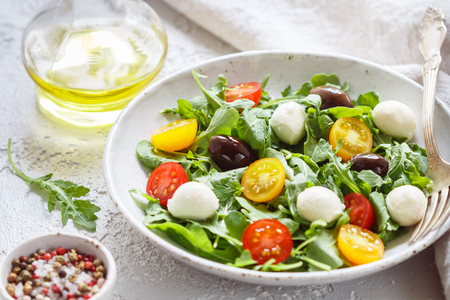 Fresh summer salad with arugula, yellow and red cherry tomatoes, Kalamata olives and mozzarella. Selective focus