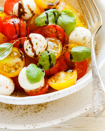 Delicious summer salad of yellow and red cherry tomatoes, mozzarella with Basil, spices and balsamic. Caprese. Selective focus