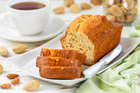 Sliced pound cake with almonds on the cutting Board. Homemade cake with nuts and honey.  Delicacy snack for tea. Selective focus 免版税图像