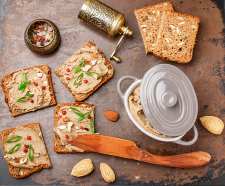 Fresh homemade chicken (duck, goose, rabbit, Turkey) liver pate with almonds, pink pepper and green onions on whole grain bread with seeds.  Traditional healthy snack for gourmets. Selective focus, top view Zdjęcie Seryjne