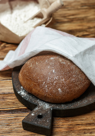 Freshly baked homemade bread, flour and a knife on an old wooden table. Rustic style. Selective focus Фото со стока