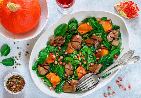 Salade tiède d'épinards avec foie de poulet, potiron au four et grenade avec épices et balsamique. Banque d'images