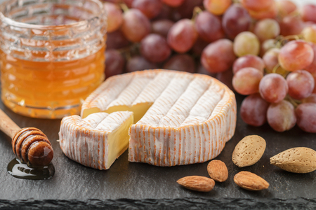 Delicatessen soft fragrant cheese with mold, honey, almonds and red grapes on a black slate plate.