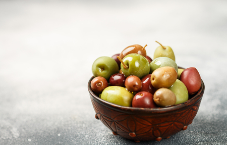 Mixed marinated olives (green and purple) in ceramic bowl.