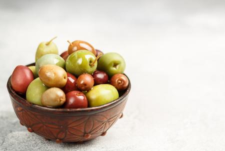 Aceitunas marinadas mixtas (verdes y moradas) en cuenco de cerámica. Foto de archivo