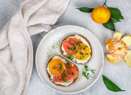 Delicious bread toasts with cream cheese (ricotta), salted smoked salmon, tangerine and pea sprouts. Gourmet snack. Selective focus Stockfoto