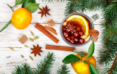Christmas mulled red wine with cinnamon, cardamom and star anise, oranges, tangerines and cranberries on an old light table.