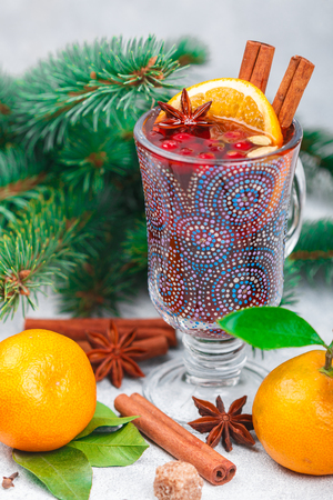 Traditional Christmas mulled red wine with cinnamon, cardamom and star anise, oranges, tangerines and cranberries on an old light table. hot drink for the New year. Selective focus