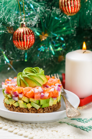 Salmon tartare (trout) with avocado and red onion on rye bread. Appetizer for Christmas and New year. A light snack for gourmets. Selective focus Archivio Fotografico