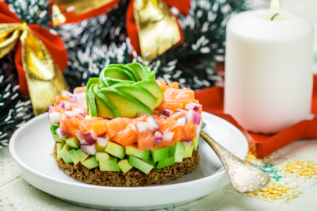 Salmon tartare (trout) with avocado and red onion on rye bread. Appetizer for Christmas and New year. A light snack for gourmets. Selective focus Banque d'images