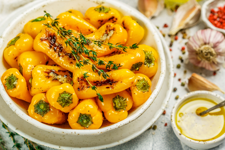 Delicatessen appetizer of roasted bell peppers with garlic, thyme and spices with olive oil. Gourmet snack.