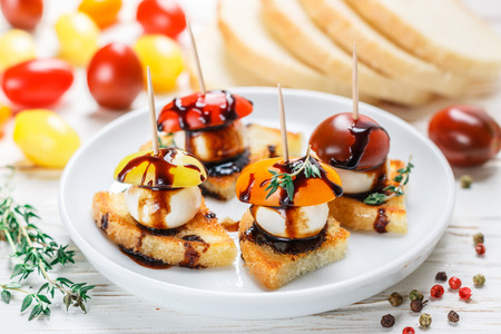 Bread toast with tomato cherry, mozzarella cheese, thyme and balsamic glaze on white wooden background. Canape. bruschetta. Gourmet snack. Selective focus Фото со стока