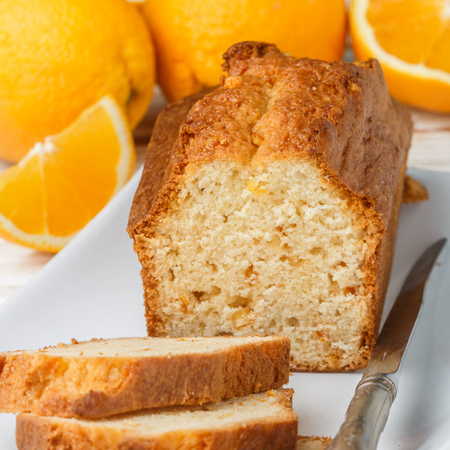 Homemade orange fruit loaf cake with citrus candied fruits and nuts.  Traditional treat for tea for Breakfast. Pound cake. Selective focus 免版税图像