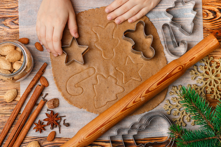 Baby's hands makes traditional gingerbread. Spices on the table-anise, cardamom, cinnamon, cloves, nutmeg, almonds. Raw dough and clippers in the form of symbols for the holiday cookies on the table. Christmas. New year