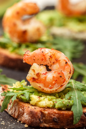 Appetizer of bread with seeds, shrimp, avocado and arugula. Crostini. Bruschetta. Sandwich. Antipasti. Selective focus