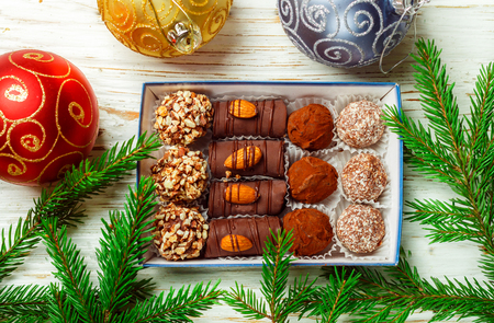 Set of chocolates. Truffles with almonds, coconut and cookie crumbs in a box on an old white table with fir branches. Gift for Christmas and New year. Gourmet. Selective focus