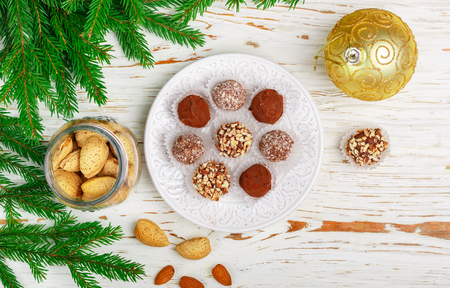 Homemade chocolate truffles with almonds, coconut and biscuits crumb in a white plate on the table with fir branches and festive toys balls. Gift for Christmas and New year. Gourmet. Selective focus, top view, copy space