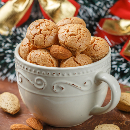 Traditional Italian almond cookies in a light Cup. Amaretti biscuits. Tasty treat for Christmas and New year. Selective focus. Square picture