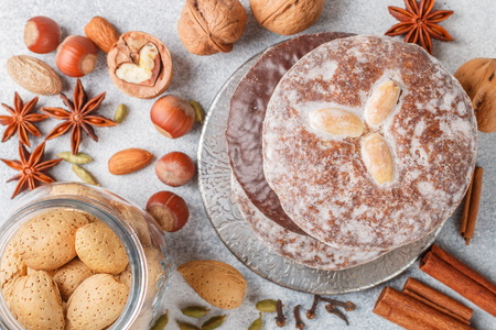 Nuremberg gingerbreads with nuts (almonds, hazelnuts, walnuts) in chocolate and sugar glaze. Lebkuchen. Traditional Christmas and new year treats. Cinnamon, anise and cardamom on the table. Selective focus
