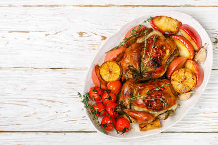 Baked whole little chickens with apples, lemon, garlic, thyme, tomatoes and spices. Selective focus, top view, copy space