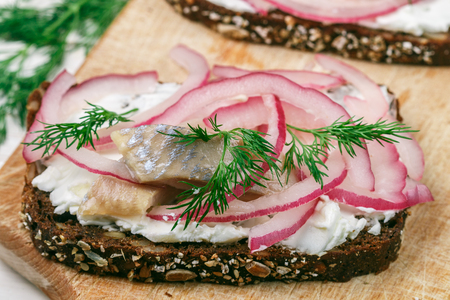 Open sandwich with salted fish herring  (mackerel), cottage cheese (ricotta), dill and pickled red onions on rye bread with seeds. Gourmet snack. Selective focus