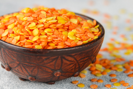 Assortment of dry multicolored lentils in a clay bowl close-up. Yellow and red cereals. Variety of grits. Delicious healthy food. Selective focus and copy space Stock Photo