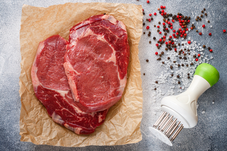 Raw fresh organic marbled meat. Beef, sea salt, pepper and garlic on the table. Rib eye steak (Ribeye Black Angus) to prepare a delicious dinner.  Selective focus Stock Photo
