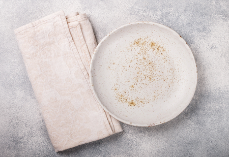 Cooking background with empty light plate and linen napkin on grey concrete table. Rustic style. Selective focus. Top view, copy space