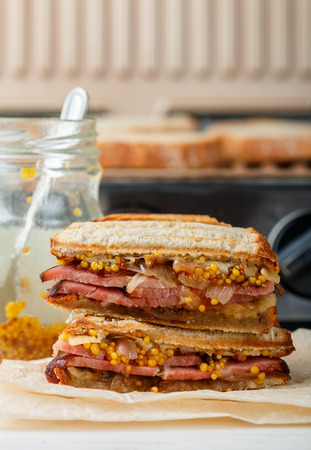 Delicious sandwich with meat, fried onions, cheese and mustard on the grill. Men's dinner. Selective focus