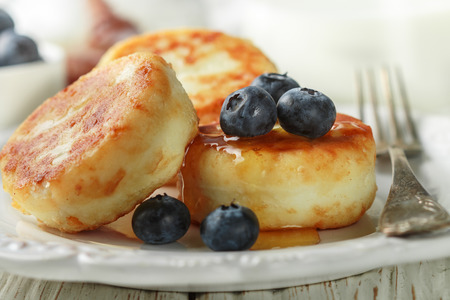 Cottage cheese pancakes, syrniki, curd fritters with fresh berries blueberry and honey in a white plate. Gourmet Breakfast. Selective focus