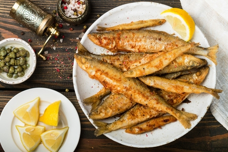 Fried smelt in a white plate. Small fish. Capers, lemon, pepper and salt on a wooden table. A delicious dinner in the rustic style. Selective focus