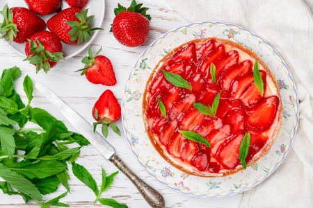 Homemade delicious strawberry tart with custard or whipped cream, with mint leaves in a plate on a white wooden table. Dessert for gourmets. Selective focus